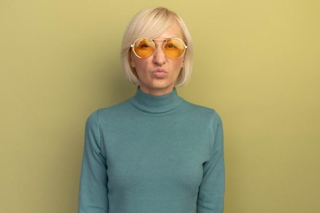 Unzufriedene hübsche blonde slawische frau in der sonnenbrille schaut kamera auf olivgrün an