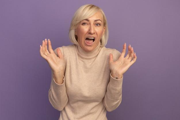 Unzufriedene hübsche blonde slawische frau steht mit erhobenen händen auf lila