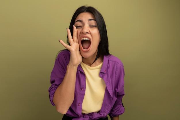 Unzufriedene hübsche brünette frau hält hand nahe zum mund und ruft jemanden an, der auf olivgrüner wand isoliert wird