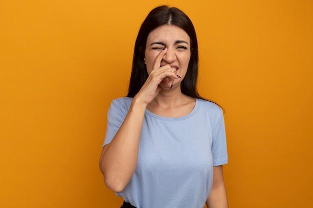 Unzufriedene hübsche brünette frau legt hand auf nase isoliert auf orange wand