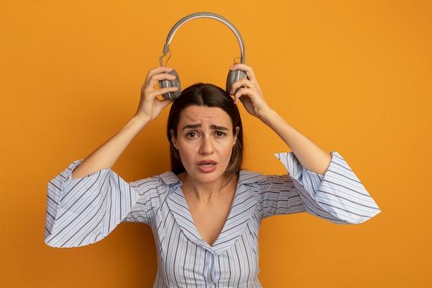 Unzufriedene hübsche frau hält kopfhörer über kopf isoliert auf orange wand