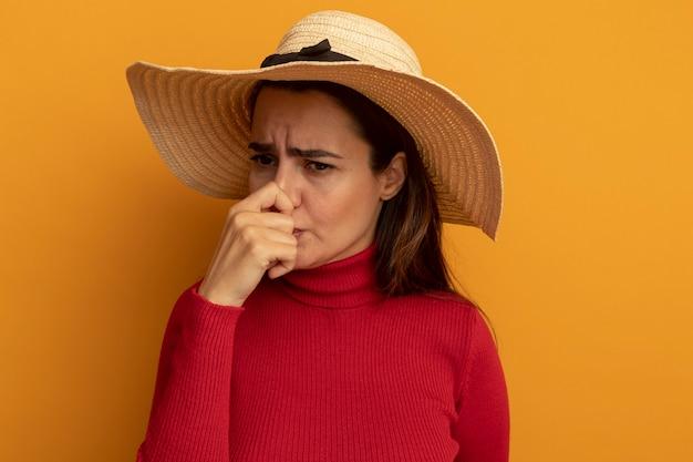 Unzufriedene hübsche frau mit strandhut hält nase isoliert auf orange wand
