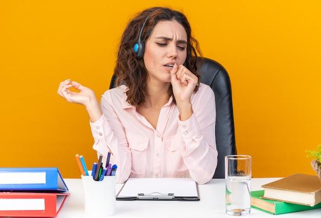 Unzufriedene hübsche kaukasische callcenter-betreiberin auf kopfhörern, die am schreibtisch mit bürowerkzeugen sitzt und die faust nahe an ihrem mund hält