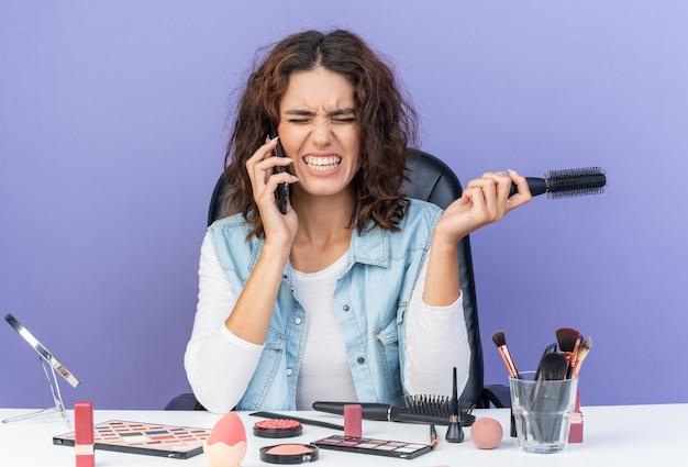 Unzufriedene hübsche kaukasische frau, die am tisch mit make-up-tools sitzt, die am telefon spricht und den kamm isoliert auf lila wand mit kopienraum hält