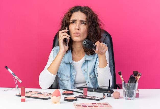 Unzufriedene hübsche kaukasische frau, die am tisch mit make-up-tools sitzt und am telefon spricht und auf die seite mit kamm zeigt, der auf rosa wand mit kopienraum isoliert ist