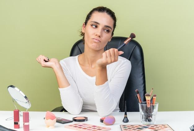 Unzufriedene hübsche kaukasische frau, die am tisch mit make-up-tools sitzt und make-up-pinsel hält und betrachtet