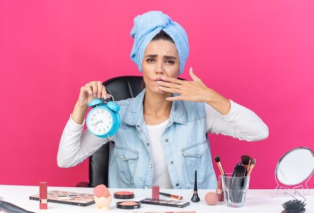 Unzufriedene hübsche kaukasische frau mit eingewickeltem haar in handtuch, die mit make-up-tools am tisch sitzt, wischt sich den mund ab und hält wecker