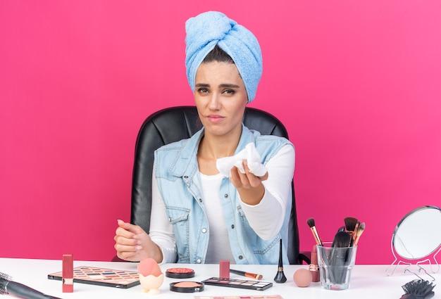 Unzufriedene hübsche kaukasische frau mit eingewickeltem haar in handtuch sitzt am tisch mit make-up-tools, die eine serviette heraushalten