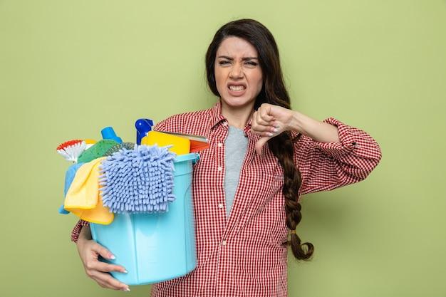 Unzufriedene hübsche kaukasische putzfrau, die reinigungsgeräte hält und runterdrückt