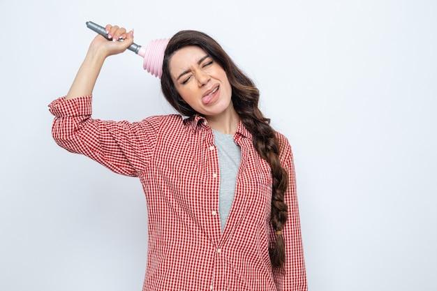 Unzufriedene hübsche kaukasische putzfrau, die sich einen gummikolben auf den kopf setzt und ihre zunge herausstreckt