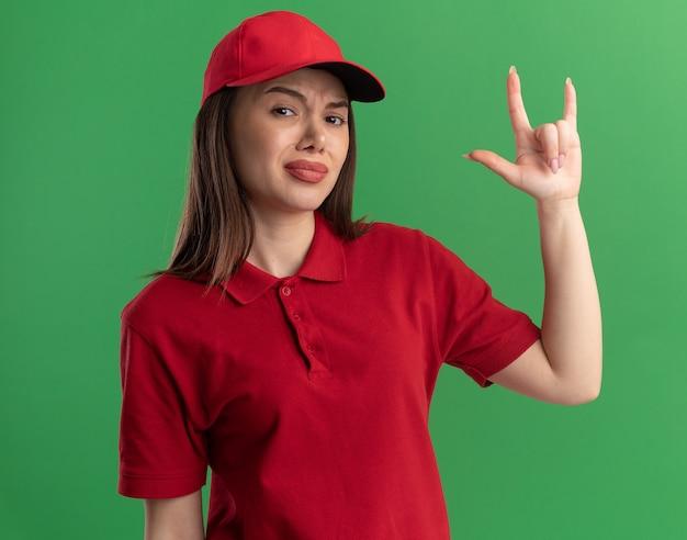 Unzufriedene hübsche lieferfrau in uniform gesten hörner handzeichen