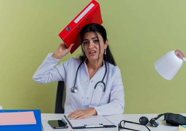 Unzufriedene junge ärztin, die medizinische robe und stethoskop am schreibtisch sitzt