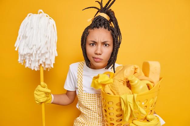 Unzufriedene junge afroamerikanerin posiert mit mop