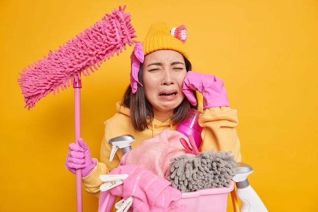 Unzufriedene junge asiatin fühlt sich sehr müde weint, da sie nicht mit der hausreinigung fortfahren möchte, hält mop lehnt sich mit schmutziger wäsche an den korb und reinigungsmittel hat eine frist, um das zimmer aufzuräumen?