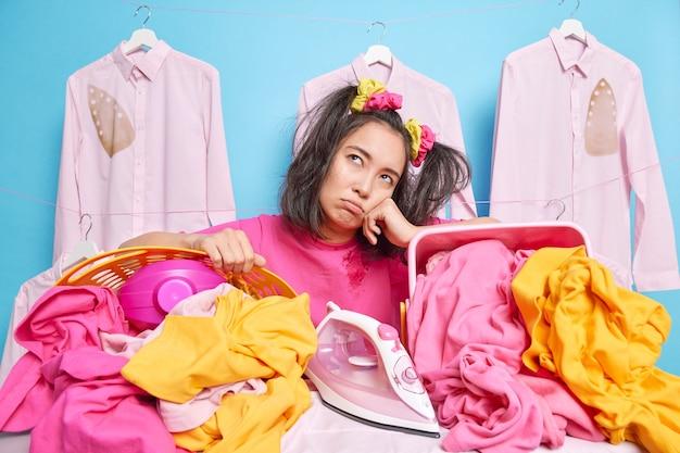 Unzufriedene junge asiatin lehnt sich an wäschekörbe, fühlt sich müde, nachdem sie hausarbeit erledigt hat, hat einen müden ausdruck