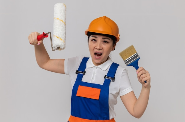 Unzufriedene junge asiatische baumeisterin mit orangefarbenem schutzhelm mit farbroller und pinsel