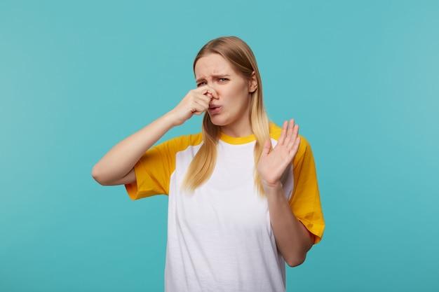 Unzufriedene junge attraktive langhaarige blonde frau, die ihre nase mit erhobener hand und stirnrunzelndem gesicht schließt, während sie schlechten geruch fühlt und über blauem hintergrund aufwirft