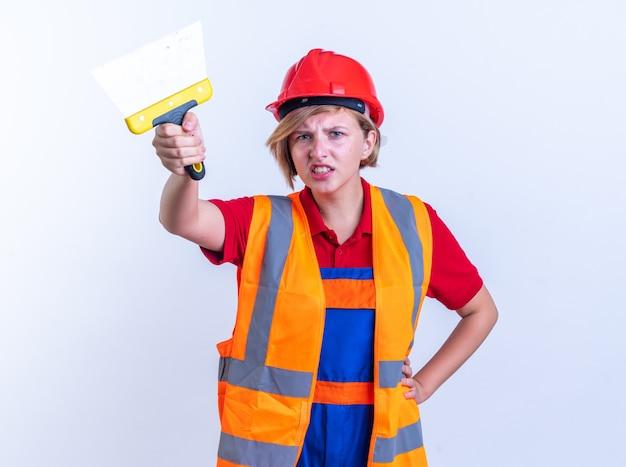 Unzufriedene junge baumeisterin in uniform, die das spachtel vorn isoliert auf weißer wand hält