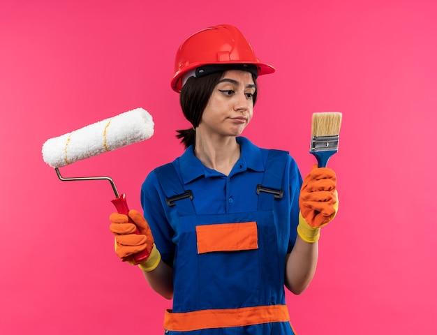 Unzufriedene junge baumeisterin in uniform mit handschuhen, die walzenbürste hält und pinsel in der hand betrachtet