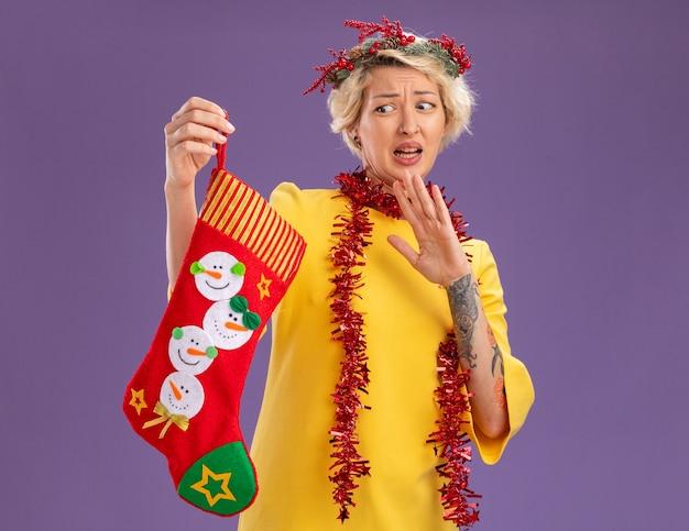 Unzufriedene junge blonde frau, die weihnachtskopfkranz und lametta-girlande um den hals hält und weihnachtsstrumpf betrachtet, der ablehnungsgeste lokalisiert auf lila hintergrund mit kopienraum tut