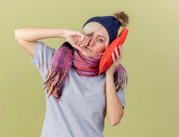 Unzufriedene junge blonde kranke slawische frau, die wintermütze trägt