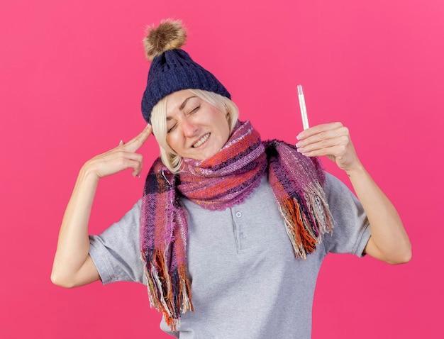 Unzufriedene junge blonde kranke slawische frau, die wintermütze und schal trägt, gestikuliert waffenhandzeichen