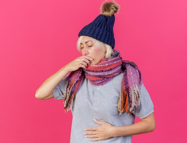 Unzufriedene junge blonde kranke slawische frau, die wintermütze und schal trägt, legt hand auf mund