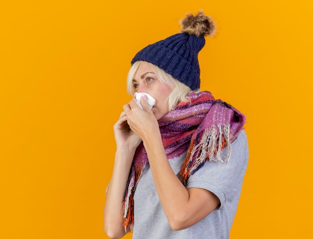Unzufriedene junge blonde kranke slawische frau, die wintermütze und schal trägt, wischt nase mit taschentuch ab, das am telefon spricht und seite betrachtet, die auf orange wand mit kopienraum isoliert ist