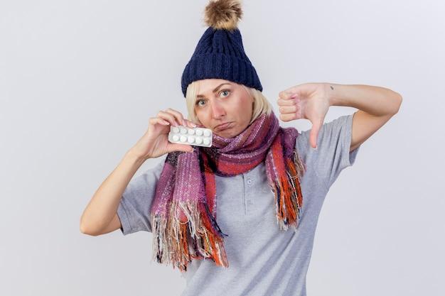 Unzufriedene junge blonde kranke slawische frau, die wintermütze und schal trägt