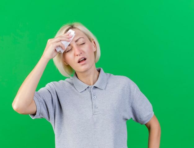 Unzufriedene junge blonde kranke slawische frau legt hand auf die stirn