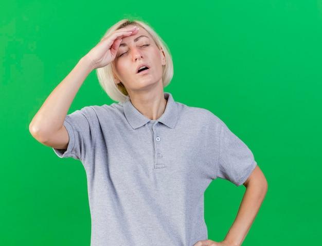 Unzufriedene junge blonde kranke slawische frau legt hand auf stirn isoliert auf grün