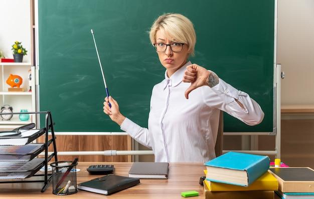 Unzufriedene junge blonde lehrerin mit brille, die am schreibtisch mit schulmaterial im klassenzimmer sitzt und auf die tafel mit dem zeigestock zeigt, der nach vorne schaut und den daumen nach unten zeigt