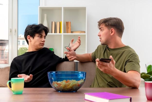 Unzufriedene junge blonde und brünette gutaussehende männer sitzen mit erhobenen händen am tisch und schauen sich den blonden mann an, der das telefon im wohnzimmer hält