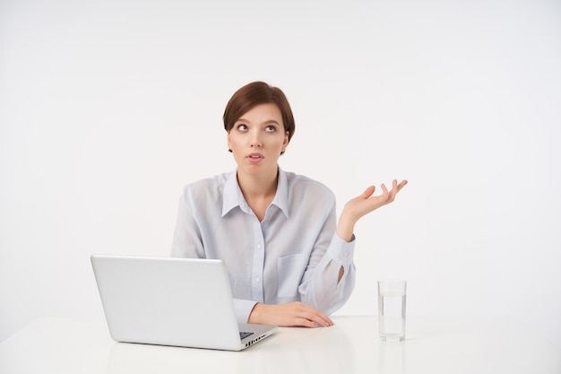 Unzufriedene junge braunäugige kurzhaarige brünette frau, die mit laptop am tisch sitzt und mit schmollmund zur seite schaut und ihre handfläche hebt, während sie auf weiß posiert