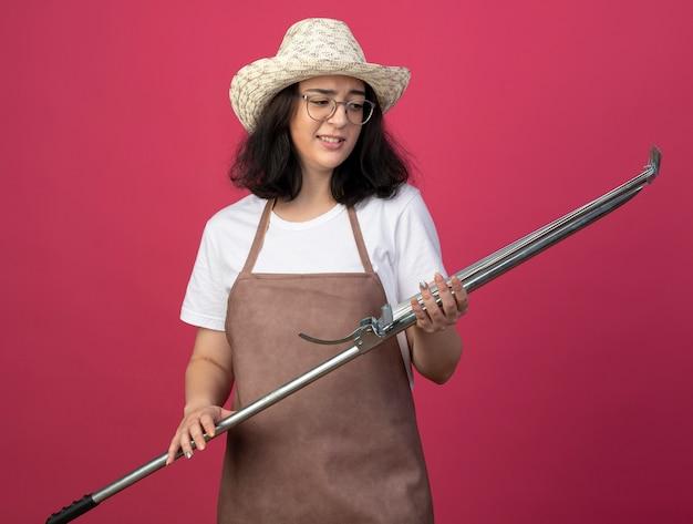 Unzufriedene junge brünette gärtnerin in optischen gläsern und in uniform mit gartenhut hält laubrechen isoliert auf rosa wand