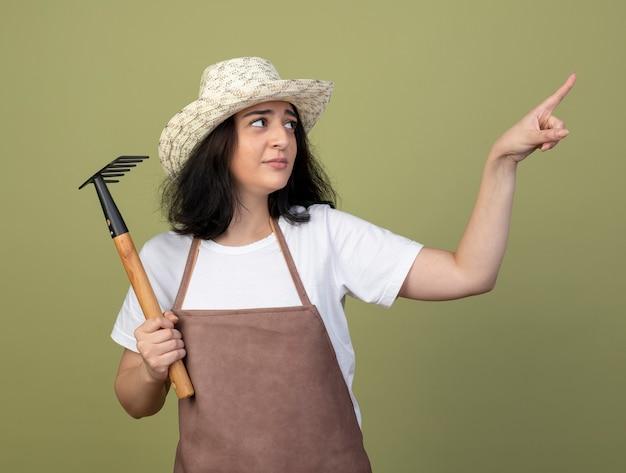Unzufriedene junge brünette weibliche gärtnerin in uniform, die gartenhut trägt, hält rechen, der auf seite lokalisiert auf olivgrüne wand schaut und zeigt