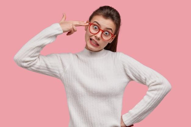 Unzufriedene junge dame imitiert schießerei, berührt schläfe, macht selbstmordgeste, trägt optische brille, hat pferdeschwanz