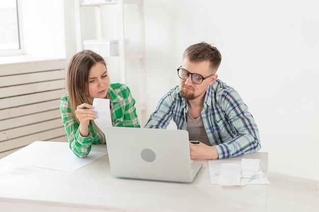 Unzufriedene junge eheleute zählen stromrechnungen für die bezahlung einer wohnung nach und schreiben die ergebnisse in ein notebook und einen laptop in ihre haushaltsbuchhaltung.