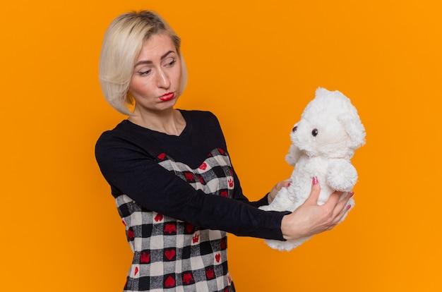 Unzufriedene junge frau, die teddybär als geschenk hält und es mit traurigem ausdruck betrachtet
