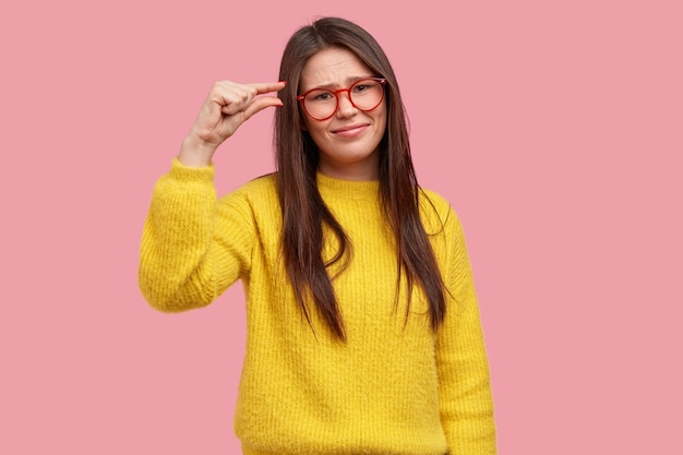 Unzufriedene junge frau hat langes haar, beschreibt größe mit den fingern, zeigt etwas kleines, trägt eine optische brille, gelben warmen pullover