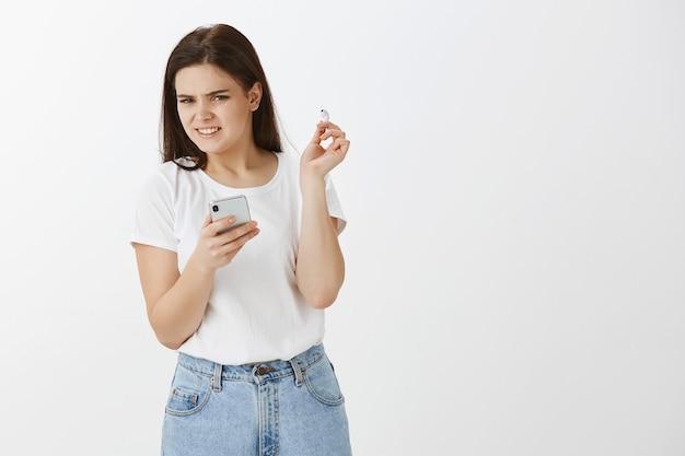 Unzufriedene junge frau posiert mit ihrem telefon und ohrhörern gegen weiße wand