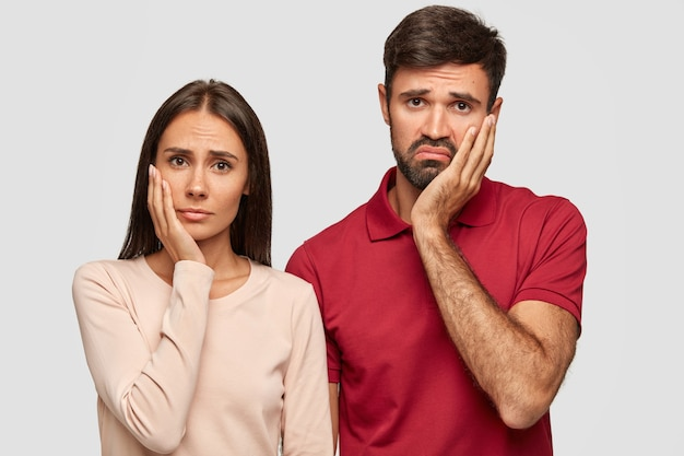 Unzufriedene junge frauen und männer halten die hände auf den wangen, schauen mit düsterem gesichtsausdruck, langweilen sich, während sie sich einen nicht interessanten film ansehen, lässig gekleidet, zeit zu hause verbringen. emotions- und personenkonzept