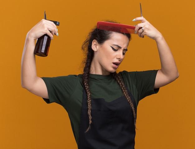 Unzufriedene junge friseurin in uniform, die haare kämmt und den kopf mit sprühflasche isoliert auf oranger wand tränkt