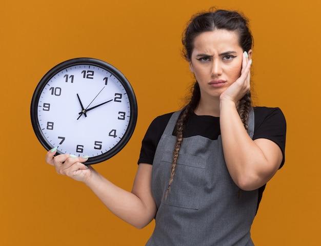 Unzufriedene junge friseurin in uniform, die wanduhr hält hand auf wange lokalisiert auf orange wand