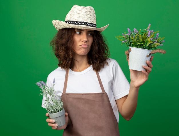 Unzufriedene junge gärtnerin in uniform, die gartenhut hält und blumen in den auf grün isolierten blumentöpfen hält und betrachtet