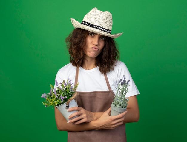 Unzufriedene junge gärtnerin in uniform mit gartenhut, die blumen in blumentöpfen hält und kreuzt, die auf grün lokalisiert werden