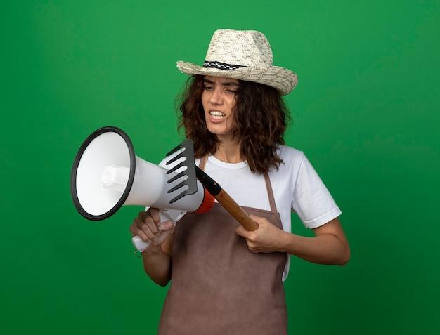 Unzufriedene junge gärtnerin in uniform mit gartenhut, die lautsprecher mit rechen hält und betrachtet