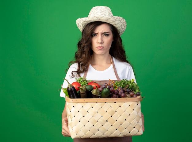 Unzufriedene junge gärtnerin in uniform mit gartenhut hält gemüsekorb isoliert auf grüner wand