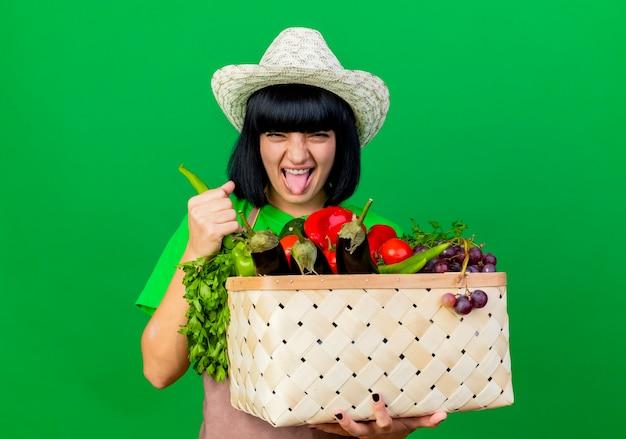 Unzufriedene junge gärtnerin in uniform mit gartenhut hält gemüsekorb und paprika