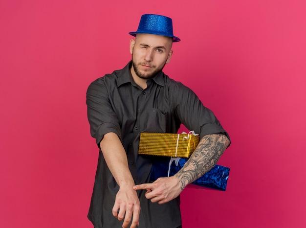 Unzufriedene junge gutaussehende slawische partei kerl, der partyhut hält, der geschenkverpackungen betrachtet kamera mit einem auge geschlossen tut, das sie tun, sind sie späte geste, die auf purpurrotem hintergrund mit kopienraum isoliert wird